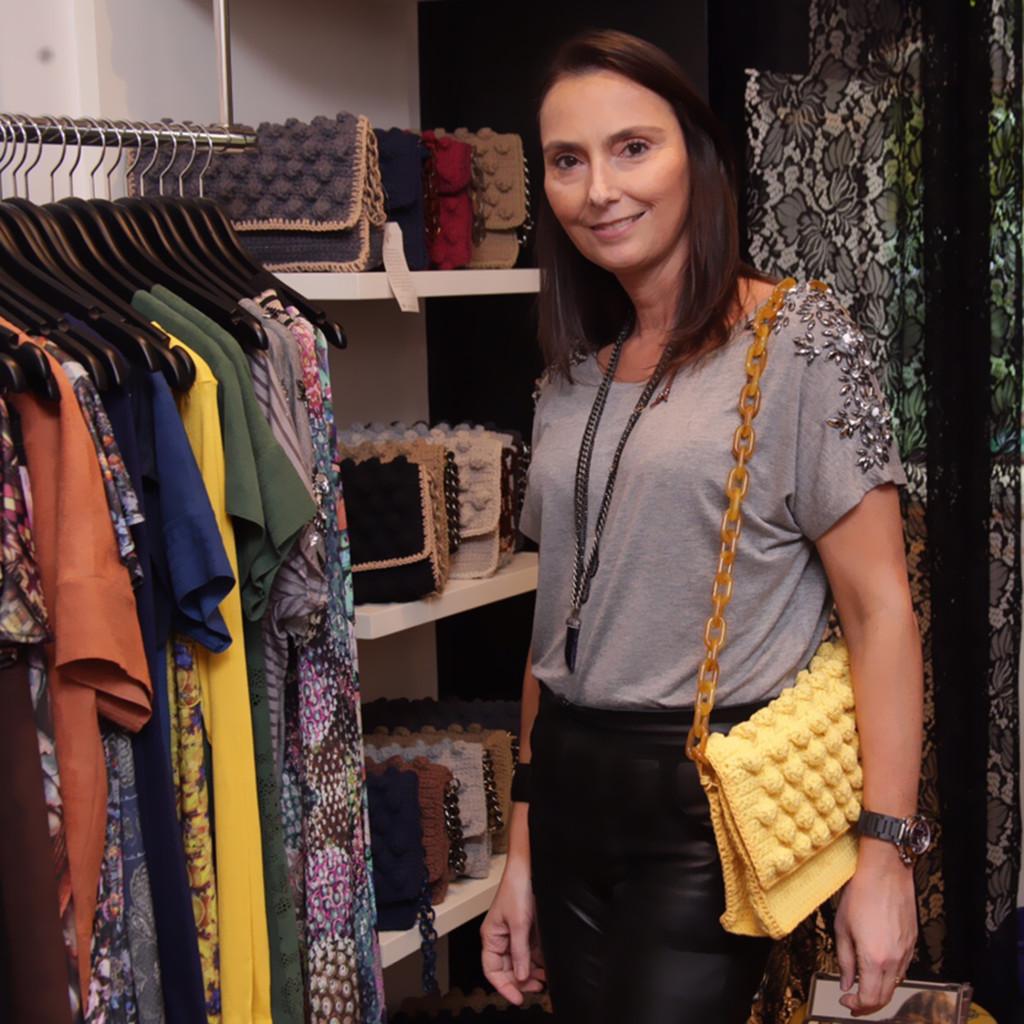 A estilista Vera Benchimol vestindo camiseta Ateliê Daniella Martins , calça de couro de sua marca e bolsa artesanal Bélier Bélier